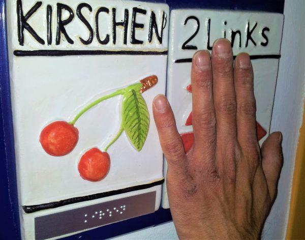 Finger tasten ein Hinweisschild ab. Auf dem Schild befinden sich Informationen als tastbares Bild, in Brailleschrift und in tastbarer Schwarzschrift. Das Schild zeigt an, welche Wohngruppen sich auf dem Stockwerk befinden.