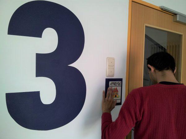 Ein Mann tastet ein Hinweisschild an einer Tür ab um sich zu orientieren. Er befindet sich in einem Treppenhaus. Die Ziffer 3 ist in Großschrift an der Wand zu sehen. Das bedeutet er befindet sich im dritten Stock